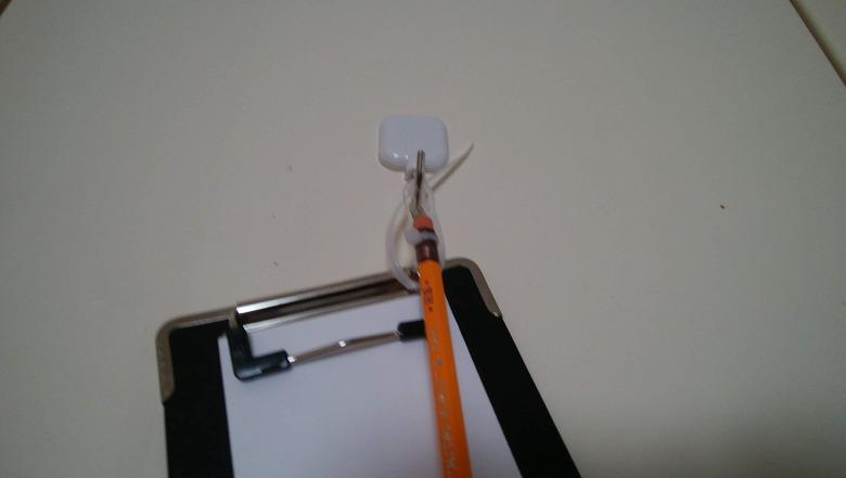 クリップボードと鉛筆をフックにひっかける